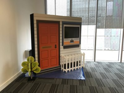 A set design of door with a TV and a fence in front