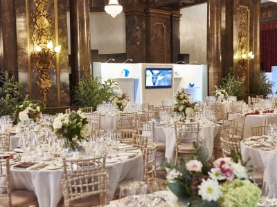 The flower arrangement on top of the reserved white tables and seats for the guests and the stage set up with flat screen tv