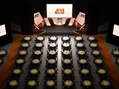 A big wide screen on a creative 3D stage set up and the reserved tables and seats for guests at AM Awards 2015