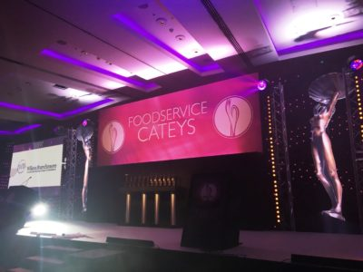 A stage design with two big statues and a poster for the Food Service Cateys Event