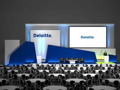 Tables and chairs for the guests and the 3D stage set up with a big screen at the Deloitte Conference