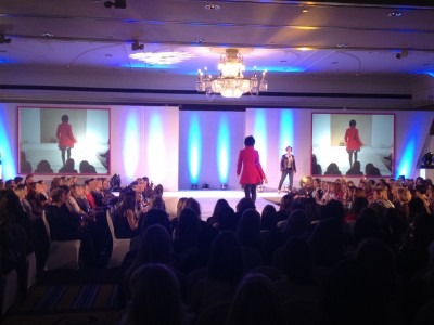 A model wearing a red trench coat posing for a fashion show event.