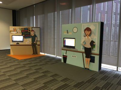 Two set designs, each featuring a television with a standee of a man and a woman