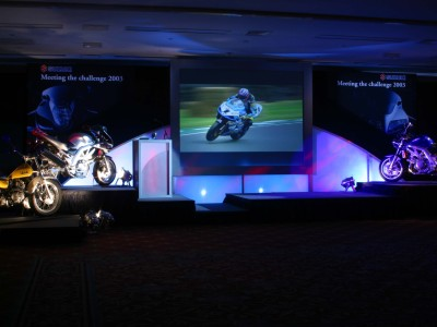 The stage set up with different motorcycle models and a flat screen tv showing a man riding a motorcycle