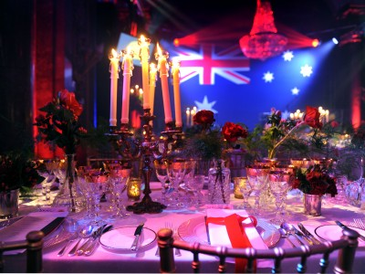 A candle holder and flower arrangement on top of the reserved table for guests at a gala dinner with an Australian flag in front