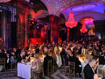 The guests eating at a gala dinner in a venue decorated with two chandeliers