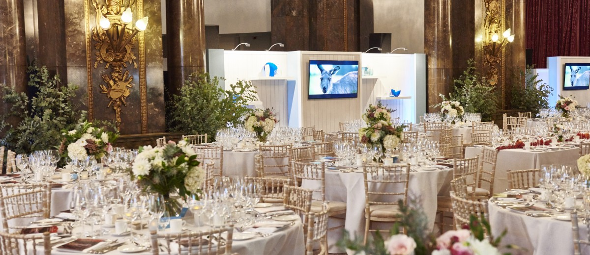 The flower arrangement on top of the reserved white tables and seats for the guests and the stage set up with flat screen tv.