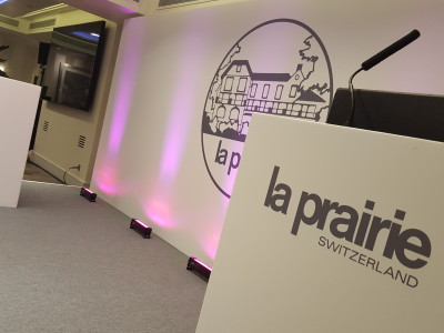Two white podiums on the corner of a stage at a La Prairie event.