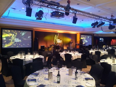Reserved table setups and a stage displaying musical instruments and LCD TV's for the British Inspiration Awards 2012.