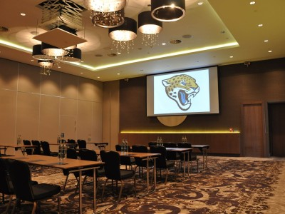 A big screen and bottled water on top of the table at the Hilton Wembley Conference Room