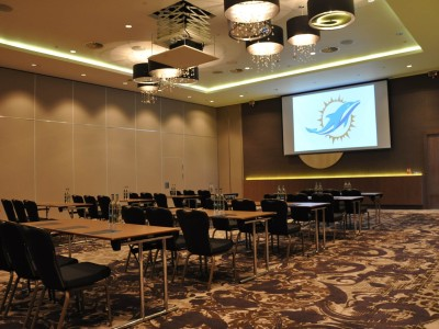 Chairs, tables and a big screen at Hilton London Wembley Hotel Conference Hall