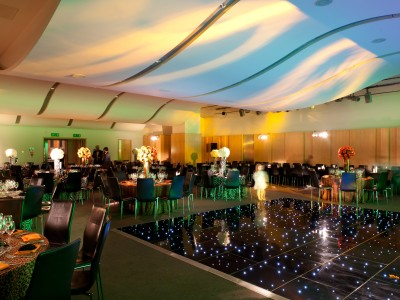 Tables and seats for guests and a dance floor with disco lights in an event at The Cumberland Hotel
