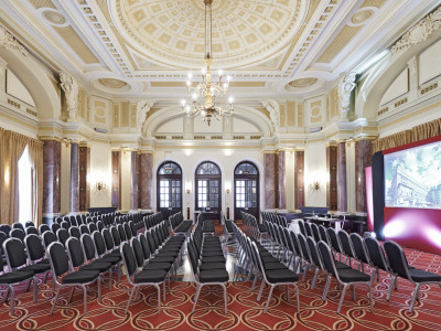 Black chairs set up at Amba Hotel Charing Cross Hotel with elegant ceiling and glittering chandeliers