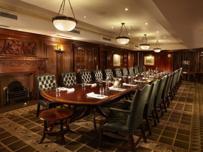 A room with a wooden furniture, long tables, and chandeliers at Amba Hotel