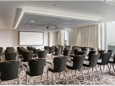 Black chairs and a big screen at Hilton Wembley Hotel Conference Room.