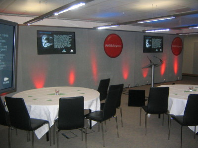 Reserved tables and chairs facing a podium and two big screens in a Coca-cola Enterprises event.