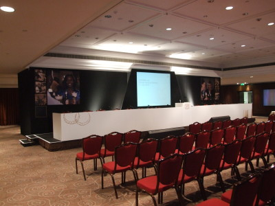 Reserved seats facing a colloquium-like stage setup with a wide screen on the center.