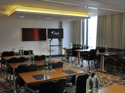 Tables, chairs and a screen at Hilton Wembley Conference room