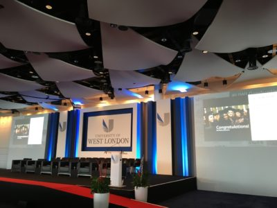 The stage setup with several black chairs for the commencement exercises of the University of London