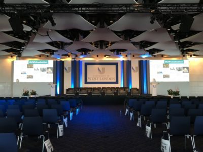 Black chairs reserved for the guests and the stage for University of London Event
