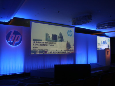 Stage setup with two big screens and dim lightings at hp Customer Forum