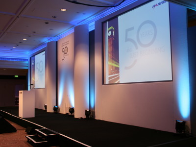 A stage setup with a podium and 3 wide screens at Intercontinental Park Lane