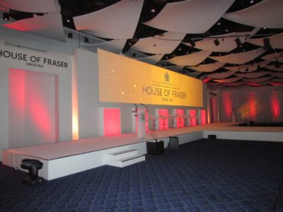 A simple stage set up with white chairs at the House of Fraser Event