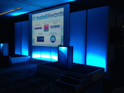 Stage setup with two podiums on both sides and a wide screen in its center in Install Awards.