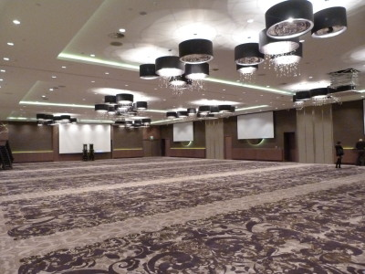 A venue displaying chandeliers, big screens, and the brown carpeted floor.