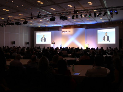 The guest speaker on a white stage setup at the Deloitte event