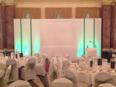 Plain white stage setup with green lights and reserved seats for the guests