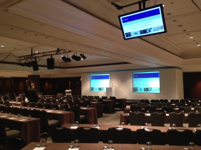 A stage setup with a rostrum and wide screens facing the reserved seats and tables.