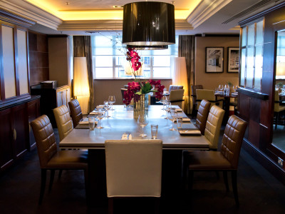 A chandelier and a dining table with flowers and wine glasses on top in the dining area of Amba Hotel