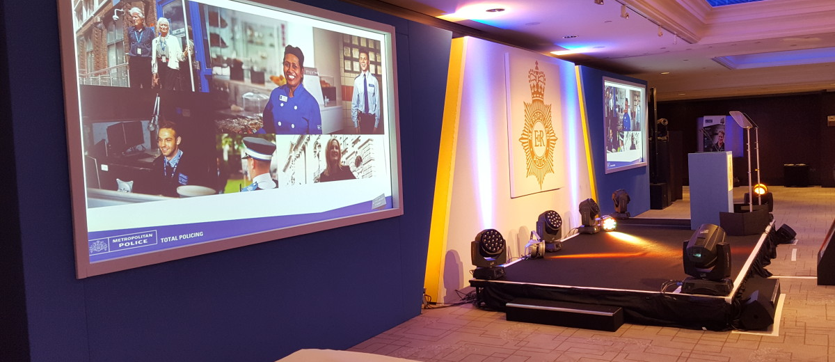 The stage setup with the Metropolitan Police logo and a rostrum on its center and a wide screen on both sides.