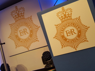 Stage setup showing the logo of the Metropolitan Police.