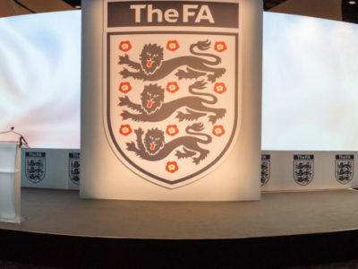 A simple stage set up with a big logo of The FA